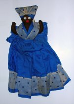 Image of Black female figure with blue and white polka dot kerchief and matching ample dress to cover a toaster with her arms upraised.