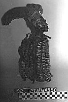 Image of Eshu figure, Shango standing devil, subject of Ifa ceremony, represents good and evil, phallic form of hair-do extends backwards, cowrie shells hang from neck, beaded long hat surmounted by bird, cowry, leather, wood, amulets among attachments.