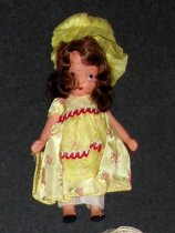 Image of Little Miss Muffet: Storybook Series #118 - Young brunette girl wears yellow flower-print dress, yellow apron, white bloomers, yellow bonnet and black slippers. Jointed arms and legs.
