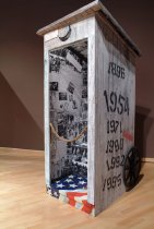 Image of REVIEW/54--Outhouse - Wooden outhouse structure with two wheels mounted on right and left exterior sides. Inside is plastered with text, photographs, a light, and audio recording. Outside shows stenciled dates.