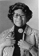 Image of photograph of mature Ella Fitzgerald wearing a black turtleneck sweater with brooch and a gingham-patterned jacket