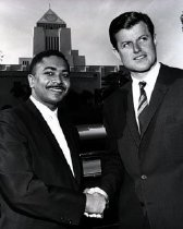Image of Mervyn Dymally shown shaking the hand of Ted Kennedy. Central Library shown in the background.