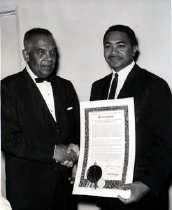Image of Assemblyman Dymally presenting a California Assembly Resolution to an unidentified man with bow tie.