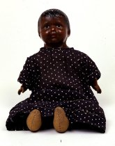 Image of Black female doll wearing navy blue and white polka dot dress.