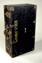Image of Foot locker trunk of golfer Bill Spiller, his name is painted on the top side. Two (2) scarves, (4) pamphlets, (4) books of matches, (1) canister of foot powder, DMV registration and No. 19 hole marker inside trunk. Interior hinge is not operational. Musty odor emits from interior.