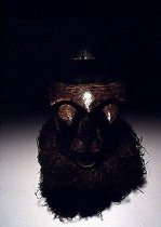 Image of Mask, helmet - Reddish brown with black highlights. Ornately carved wooden mask with large protruding eyes and nose. Forehead has sharp ridge with round projection atop head as ornamentation raffia embellishes bottom of mask at neck with multi-triangular design around protruding mouth. Exceptional.