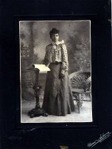 Image of Smartly dressed standing African American woman, posed with her hand turning pages in a book with a chair behind her. Backdrop displays an outdoor staircase.