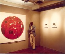 """Image of Clay Painting Exhibition--Los Angeles City College Gallery - Photograph of ceramicist Doyle Lane with his """"clay paintings"""" on display in a gallery within Los Angeles City College. Lane stands to the right of one of his larger works of art."""