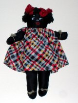 Image of Rag doll wears checkerboard print dress with red yarn bows in hair.