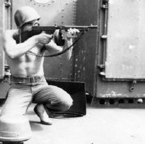 Image of 1985.0069.94 - B&W photo of sailor with gun / rifle  Tommy Gun on USS Clemson