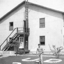 Image of 1986.0008.1.2 - B&W of Ray in front of barracks in Virginia
