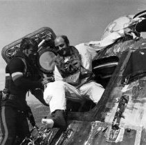 """Image of 1991.0014.37 - B&W photo. A Navy frogman assists Apollo 17 astronaut Cmdr. Ronald Evans as he climbs out of the command module """"America"""" following the splash down. Evans served as they command module pilot for the mission"""