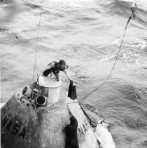 Image of 1991.0014.38 - Color photo.  Underwater Demolition Team members prepare to secure a cable from a crane to a dummy command module as a practice for the recovery of the Apollo 15 space capsule. The men are from the amphibious transport dock USS Austin (LPD-4).