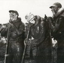 Image of 2001.0050.1 - B&W photo of men covered in mud.  Screaming or yelling, one looks asleep standing up.