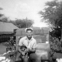 Image of 2001.0080.39 - B&W photo of sailor with puppy on Jeep