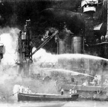 Image of U.S. sailors man boats at the side of the burning U.S.S. West Virginia