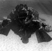 """Image of 2000.0044.30 - B&W photo of Lt. John Booth wearing LARU, showing Lambertsen technique. """"Self-Contained Breathing Apparatus from which U.S. Self-Contained Diving Evolved."""""""