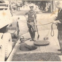"Image of P2014.014.001 - Photo shows how Jamestown's ""catch basins"", downtown, were kept clean around 1950"