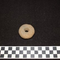Image of Gabbro Doughnut Stone--view A, pecked ventral side with perforation.