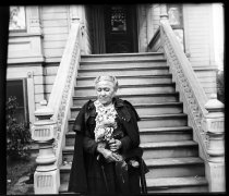 Image of Older woman sitting on steps of house
