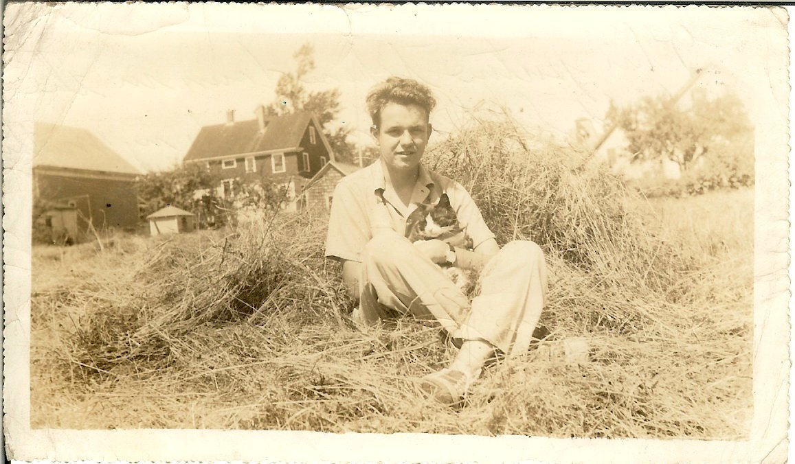 young Paul Hinton sitting in a field with a cat