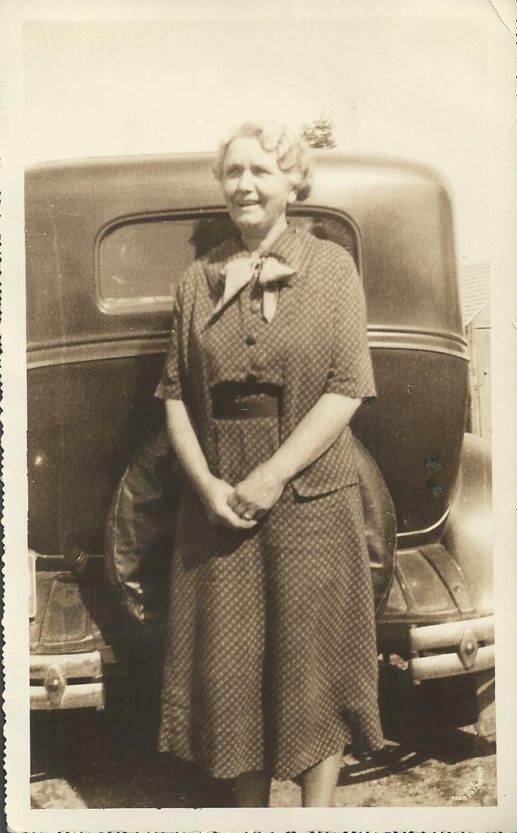 Esther Gott, standing near automobile