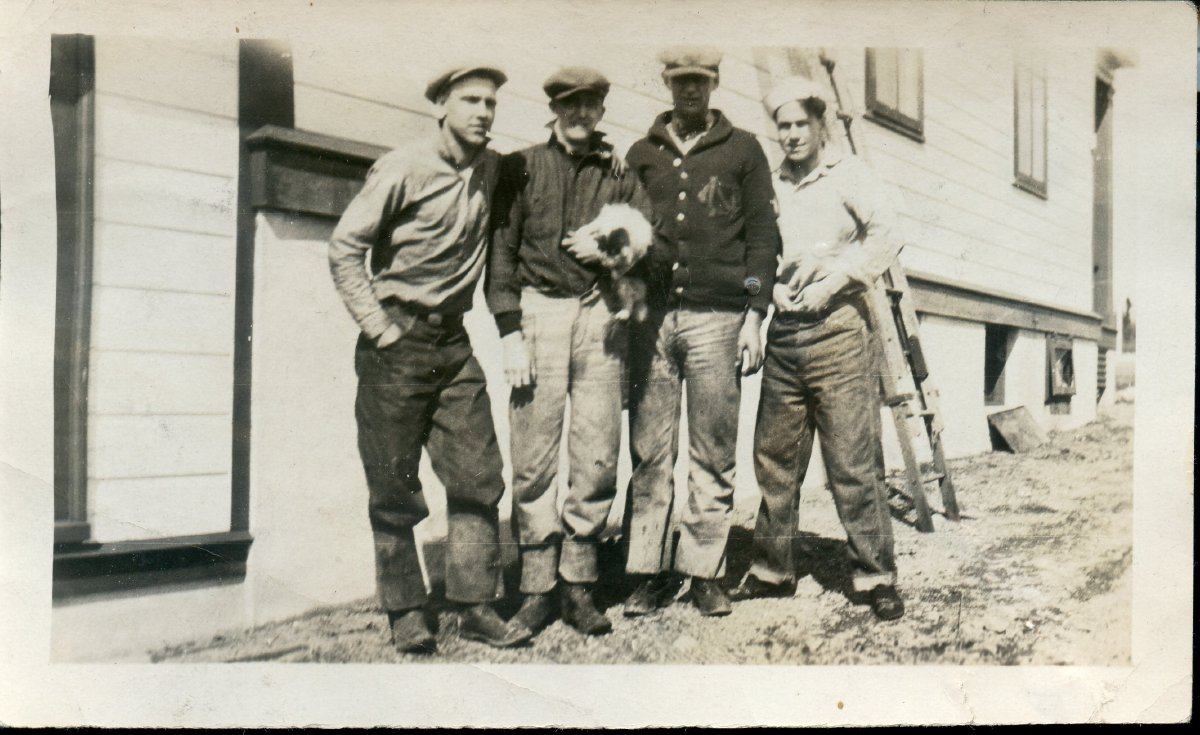 4 men standing outside a building