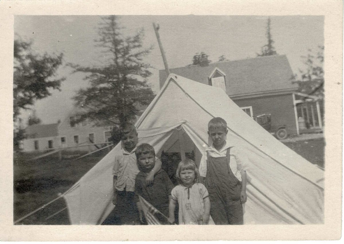 Four children outside their tent near old red store