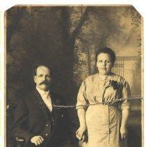 Image of Woman standing beside sitting man. -