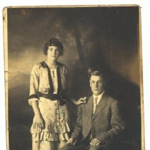 Image of Woman standing next to man sitting in chair -