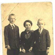 Image of Sitting woman with two young boys. -
