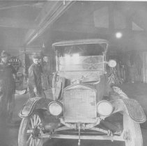 Image of Hugo Johnson, Dick Berntsen, and a third man work on an early motorcar -