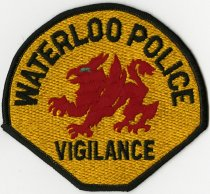 """Image of 2013.07.14 - Cloth embroidered emblem with """"Waterloo Police Vigilance"""" written on it in black against a yellow background. In the center is a red winged and clawed creature with a blue eye."""