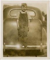 Image of Young boy standing on a car's rear bumper - John Martin Smith Miscellaneous Collection