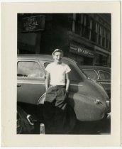 Image of Young man leaning against an automobile - John Martin Smith Miscellaneous Collection