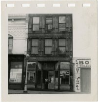 Image of A man stands in the doorway of an old storefront - John Martin Smith Miscellaneous Collection