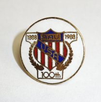 "Image of 2014.12.06 - This is a pin showing a red, white, and blue shield with USA in the center. Printed in the top portion of the shield is: ""1888"" ""AAU"" ""1988"". At the bottom: ""100th""."
