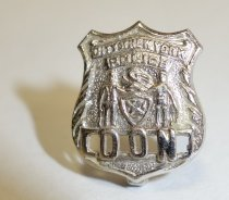 "Image of 2014.12.06 - This is Don Lash's silver shield pin, which has ""City of New York Police"" at the top, and ""DON"" at the bottom."