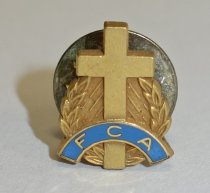 "Image of 2014.12.06 - This is Don Lash's Fellowship of Christian Athletes pin, which is decorated with a cross, a partial wreath, and a blue banner marked with the letters ""FCA""."