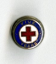 "Image of 2014.12.06 - This is a Red Cross pin, edged with a blue border that contains the words ""Five Years."""
