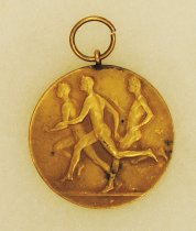 Image of 2014.12.06 - This is a fourth gold medal from Don Lash's collection that shows 3 runners on the front and an emblem with ICAA on the back.