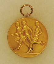 Image of 2014.12.06 - This is a fifth gold medal from Don Lash's collection that shows 3 runners on the front and an emblem with ICAA on the back