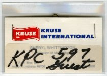 "Image of 2016.06.01 - Affixed to this Kruse International business card for Sheryl Whittington, Director of Marketing is an adhesive label with the handwritten text ""KPC 597 Guest."" Whittington's name and position are visible through the label and the business card has a partially obscured Auburn, Indiana address and a telephone number. The card is stapled within a plastic carrier with a safety pin clip for use as an id badge."