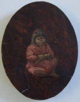 Image of 1967.019 - Indian Child with Bedindle Whorl by Lavinia B. Hill, c. 1920-1967.  Oil on redwood.  Image depicts American Indian woman of a San Diego tribe.  She is wearing a long-sleeved red dress with white flecks and is barefoot.  She is seated, on the ground with her left knee raised.  In her hands she holds a spinning whorl.  Image is painted directly onto an oval piece of redwood.  A clear layer of varnish covers the entire front.