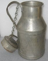 "Image of 1974.356 - Milk Can, c. 1920s-1950s. Steel Milk Can has a cylindrical body that tapers inward to a narrower cylindrical spout.  Spout has a curved lip.  There is a handle soldered to spout and base of angled section of body.  A chain is mounted to hole top inside curve of handle and also to hole in handle of lid.  Lid has a cylindrical body that rests inside neck of can and a wider top that tapers inward on sides.  Horizontal handle is soldered to tapered sides of lid.  Embossed on side of can is ""MEADOW GLEN D  /  SF."""