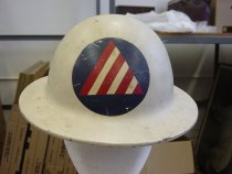"Image of 1977.248.001 - Civil Defense Air Raid Warden Helmet, c. 1942-1945. This metal helmet is round in shape and is painted in gray. In front of the top center portion of the helmet's head, there is a blue circle with a red/white striped triangle, which is the symbol for Civil Defense Air Raid Warden. On the back of the helmet on the outside border, it is surrounded by metal bracket ends painted in white with each of them are tied to a brown cloth strap, which is connected to a black fabric circle in the middle. Surrounding in the middle, above the black fabric circle, is a brown leather head strap, which covers the portion of the head in the helmet. On the left and right metal ends of the helmet, the brown cloth straps are connected to a brown small leather chinstrap with a small metal loop bracket used for adjusting the strap on to the chin, and a metal nail holding the chinstrap together.  In the middle of the inside of the helmet, in a red circle with a single white star, the painted text in blue says ""Mfd. by  /  LOS ANGELES"".  The words ""LOS ANGELES"" are in bold. In between the red circle, in white outer border with a blue background, in white, the painted text says ""B.F. McDonald CO."" The words ""McDonald"" is disproportionately bigger than the rest of the text above."