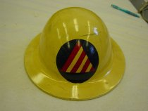 "Image of 1977.248.002 - Civil Defense- Air Raid Warden Helmet, c. 1947-1991. This metal helmet is round in shape and is painted in yellow. In front of the top center portion of the helmet's head, there is a blue circle with a red/white striped triangle, which is the symbol for Civil Defense Air Raid Warden. At the bottom portion of the back of the helmet, there are bolts painted in white that connect to the helmet's head and chinstrap adjustments and are spread out on each corner of the metal helmet. At the back of the helmet, there are bolts painted in white that connect to the helmet's head and chinstrap adjustments and are spread out on each corner of the metal helmet.  Inside the middle of the helmet, the white painted bolts are connected to metal brackets that are slightly bent, in which connects to a head adjustment made of leather that covers the head. The leather head adjustment is next to and parallel to the straps of white fabric which is tied to a circle made of black fabric. The middle straps of the white fabric are tied to a brown chinstrap with a metal loop bracket adjustment for the chin with a metal nail holding the strap. The chinstrap also has a metal black circle on each end that connects it to the slightly bent metal brackets on each left and right end of the metal helmet. At the bottom front portion of the back of the metal helmet, engraved in white and bold, the text reads ""...No  217714  /  No  D113432..."". At the bottom portion of the back of the metal helmet, engraved in white and bold, the text reads ""PATENTS ENDING  /  MCDONALD CO  /  LOS ANGELES""."