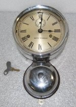 "Image of 1986.091 - Silver colored brass metal clock with bell beneath that chimes every 30 minutes.  Silver colored brass face has black hands, Roman numerals and a second hand clock beneath XII.  Wood backing has original label behind clock and Peninsula Clock Shop, San Mateo sticker behind bell.  Loose key and washer.  Silver colored metal mounting brackets attached to back at top and bottom.  ""SETH THOMAS"" printed on face.  Strike lever on left still rings bell although clock is no longer working."