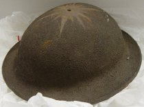 Image of 1996.226 - M1917 Helmet, c. 1917-1918. Round metal helmet, brown in color. At top of helmet head is a starburst engraving at the center.  A bolt goes through the top of the helmet to connect the head adjustment contraption.  The rounded helmet flattens at the edges with a folded over seam of metal.  The head adjustment contraption is black leather on the outer edges and tan leather on the inside.  The black leather is connected to tan cloth net webbing to adjust size of head adjustment contraption for a snug fit on the wearer's head.  The center adjustable net webbing is also used to adjust size.  A leather chin strap in attached to the inner sides of the helmet by a riveted metal ring on either side.  The leather chin strap has a metal buckle to adjust strap.