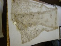 Image of 1997.221.001 - Scarf, 1861 - 1897.  Pale mauve gray and cream embroidered and beaded scarf.  Base of scarf is a micro net tulle in pale gray.  Outer border contains scrolling branches and multiple types of small multi-petaled flowers, accented with dark gray beads.  Each end of scarf has a central mirrored pattern of large curling scrolls trimmed with flowers.  Across the center of the scarf is a scattering of 14 flower and leaf motifs.  